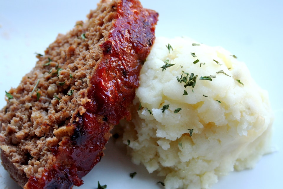 meatloaf leaning on a mound of mashed potatoes