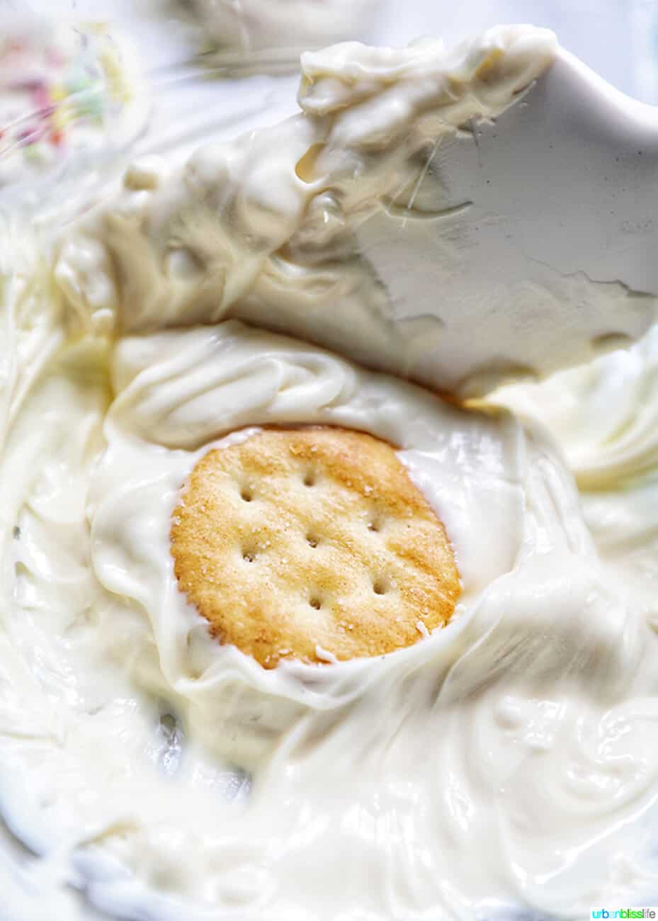 dipping Ritz cracker cookies into white chocolate