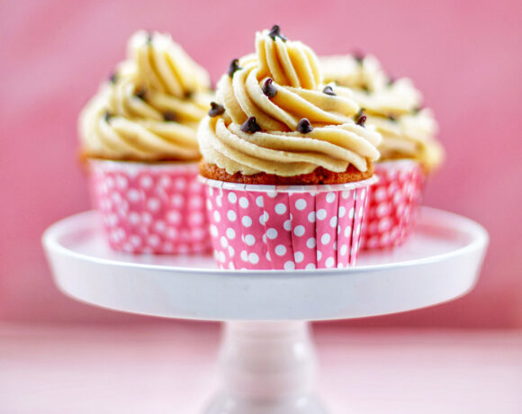Three Chocolate Chip Cupcakes with Cookie Dough Frosting on a white cake pedestal with pink background