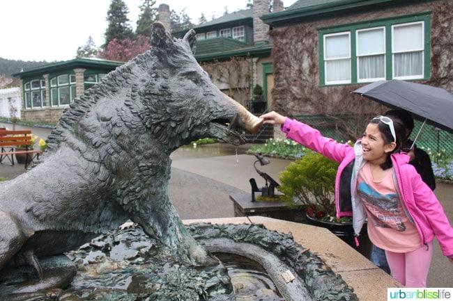 girl touching boar statue at Butchart Gardens