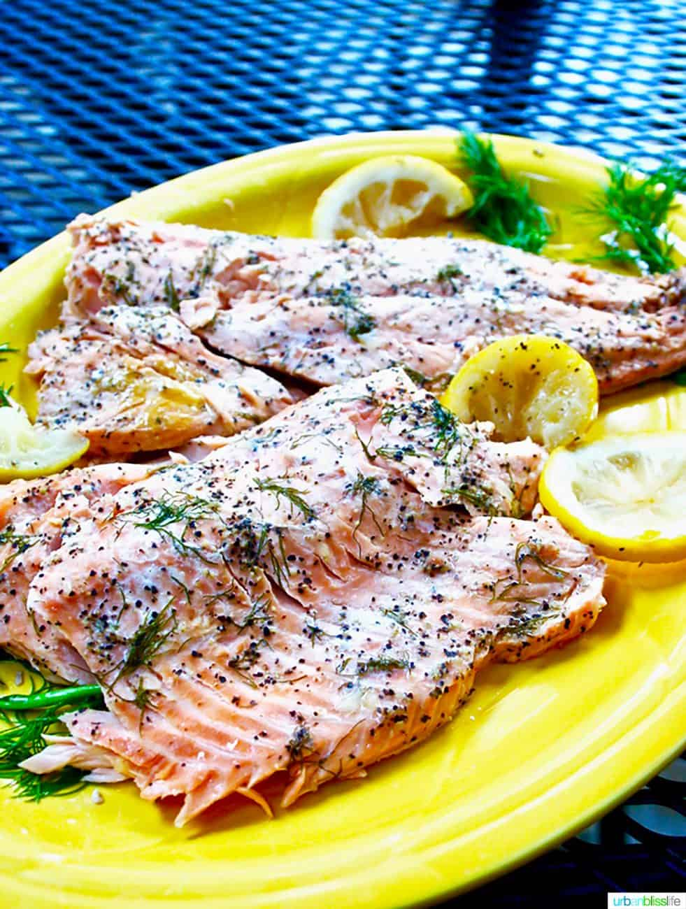 grilled salmon on a yellow platter with lemon