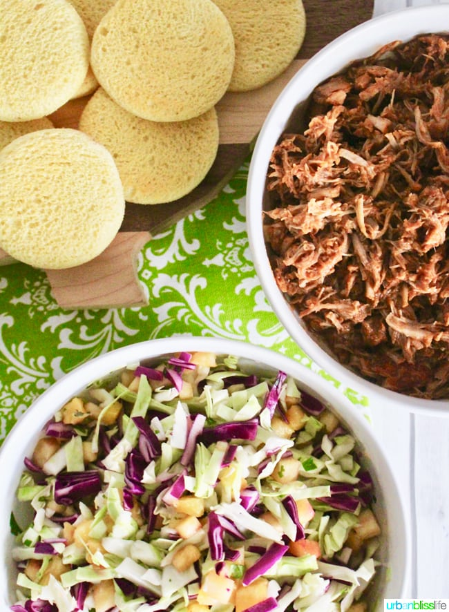 rounds of hawaiian bread, bowl of pulled pork, and plate of pineapple slaw