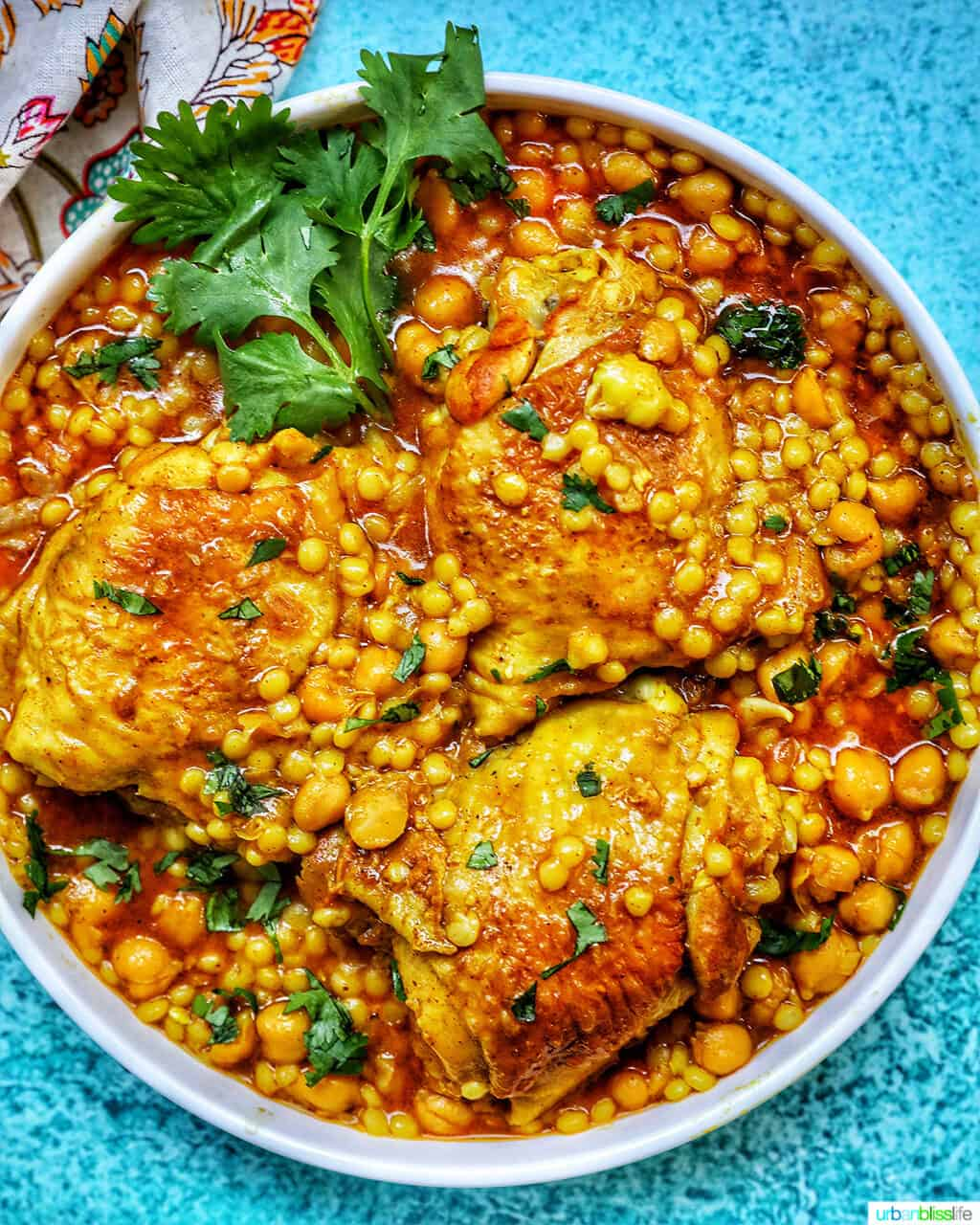 Instant Pot Moroccan Chicken in a large serving bowl with blue background