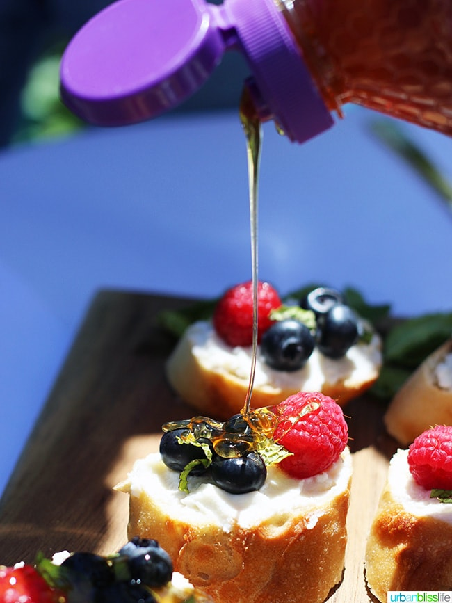 honey drizzling over berries and ricotta crostini