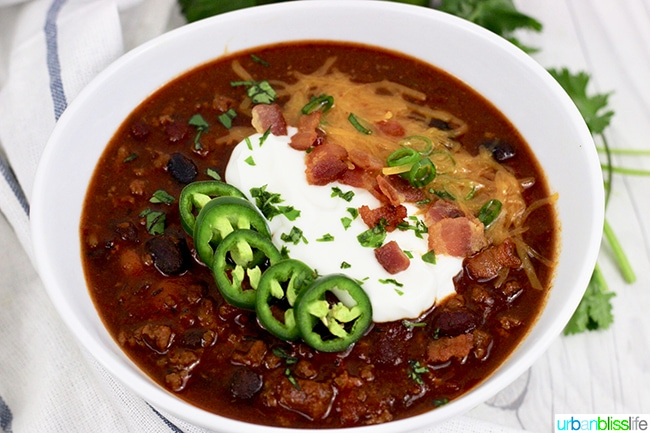 chili in bowl with bacon, sour cream, and peppers