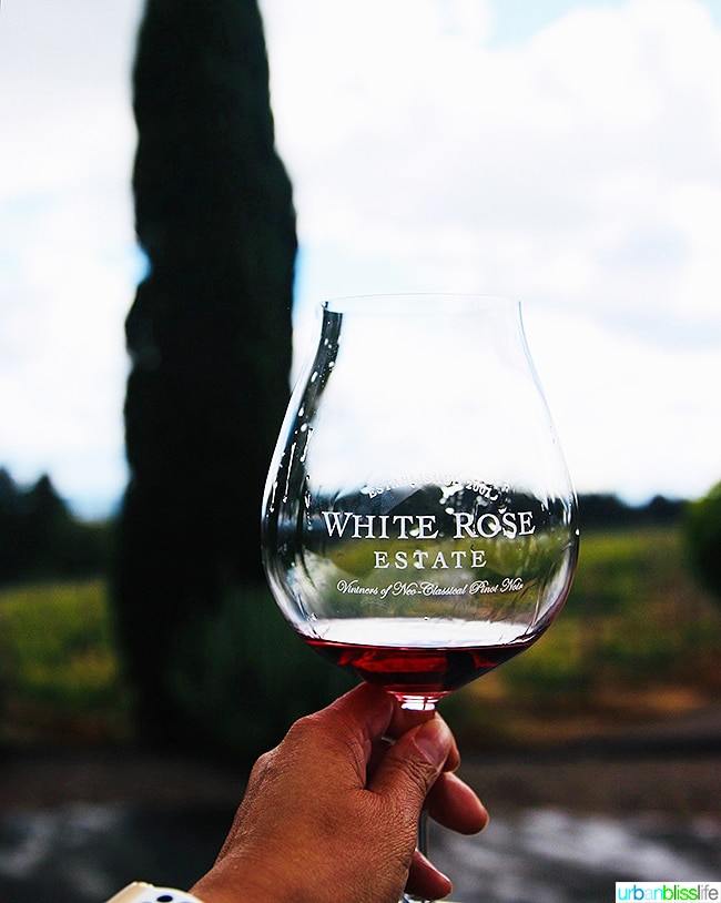 holding up a Pinot Noir glass with White Rose Cellars red wine
