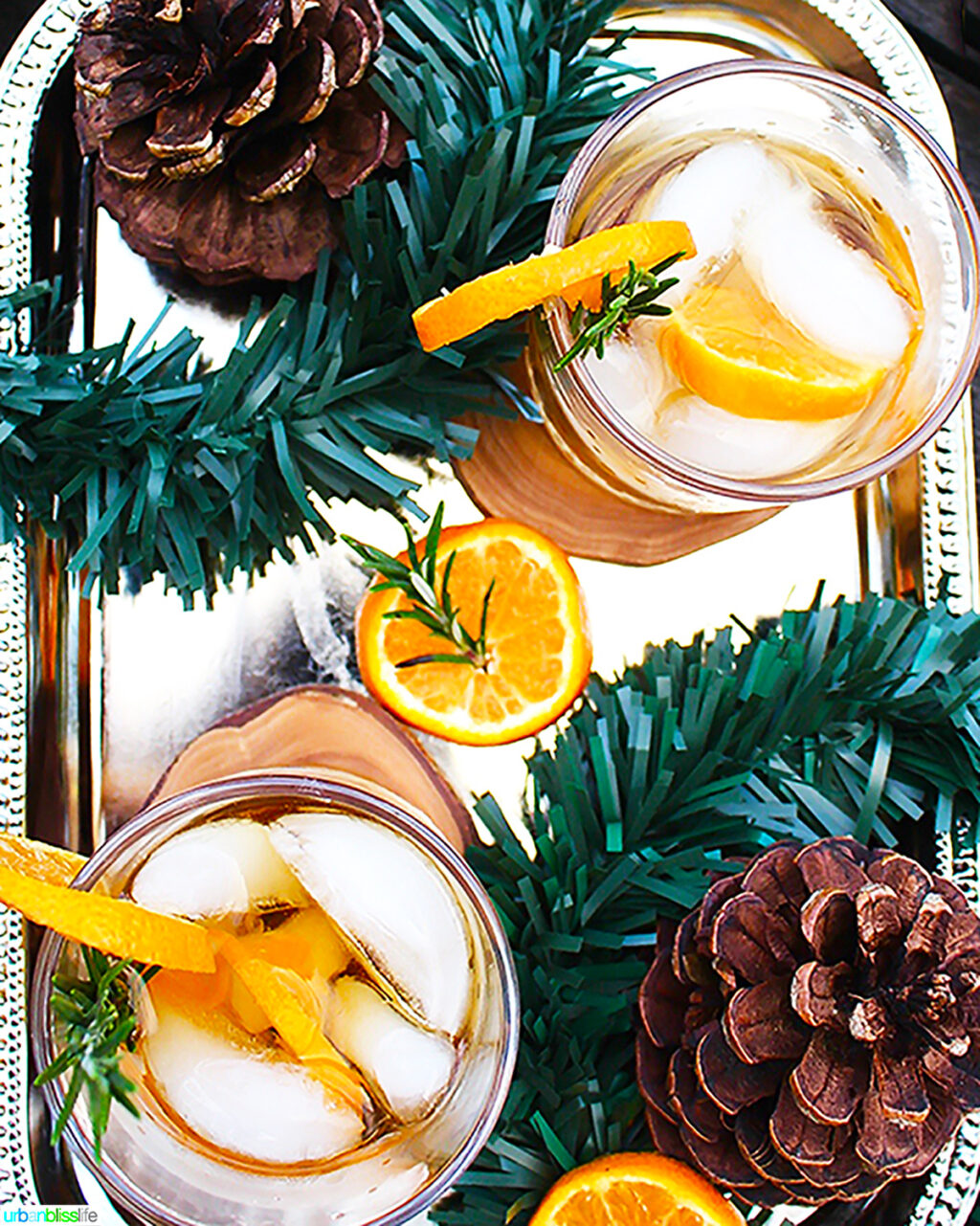 two glasses of rosemary citrus old fashioned cocktails with decorations