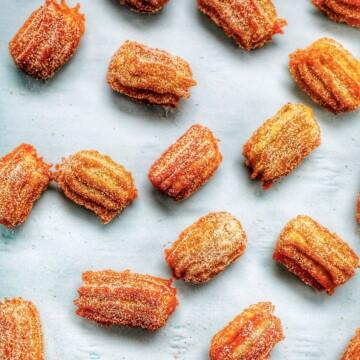 flatlay of churro bites sprinkled on a sheet