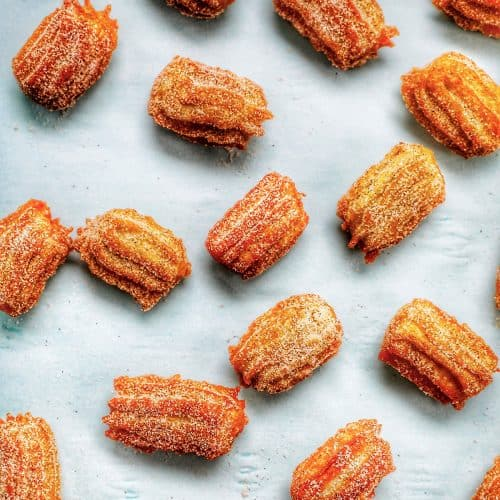 flatlay of churro bites sprinkled on a sheet