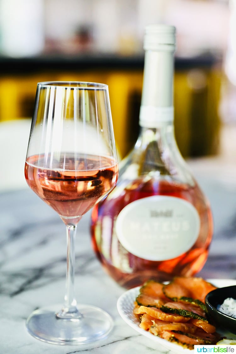 Mateus Rosé wine glass and bottle behind it