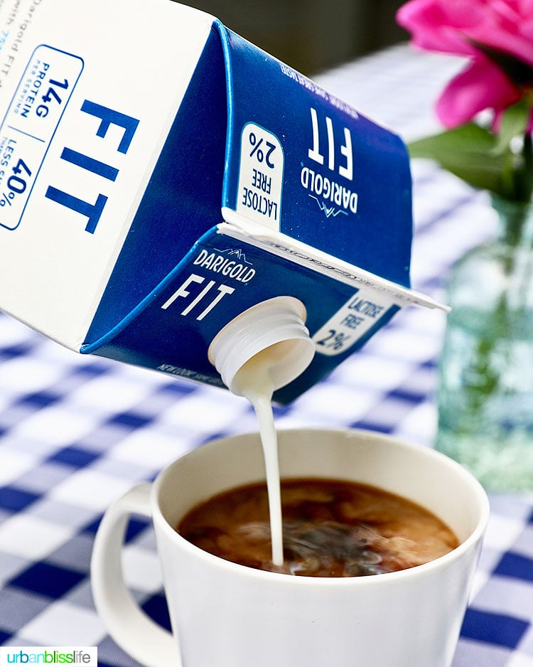 pouring ultra-filtered milk into a cup of coffee