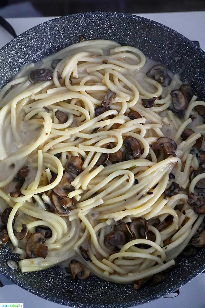 adding cream to pasta and mushrooms