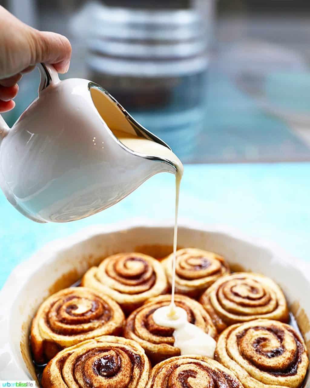 pouring icing over orange cinnamon rolls