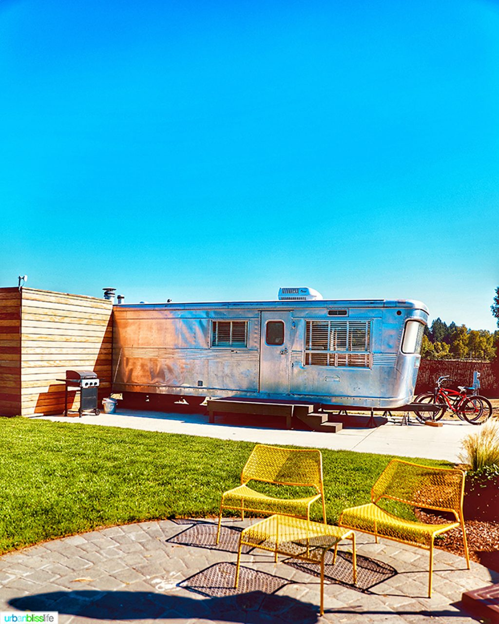 Exterior of the mansion airstream and yellow chairs at Vintages Trailer Resort