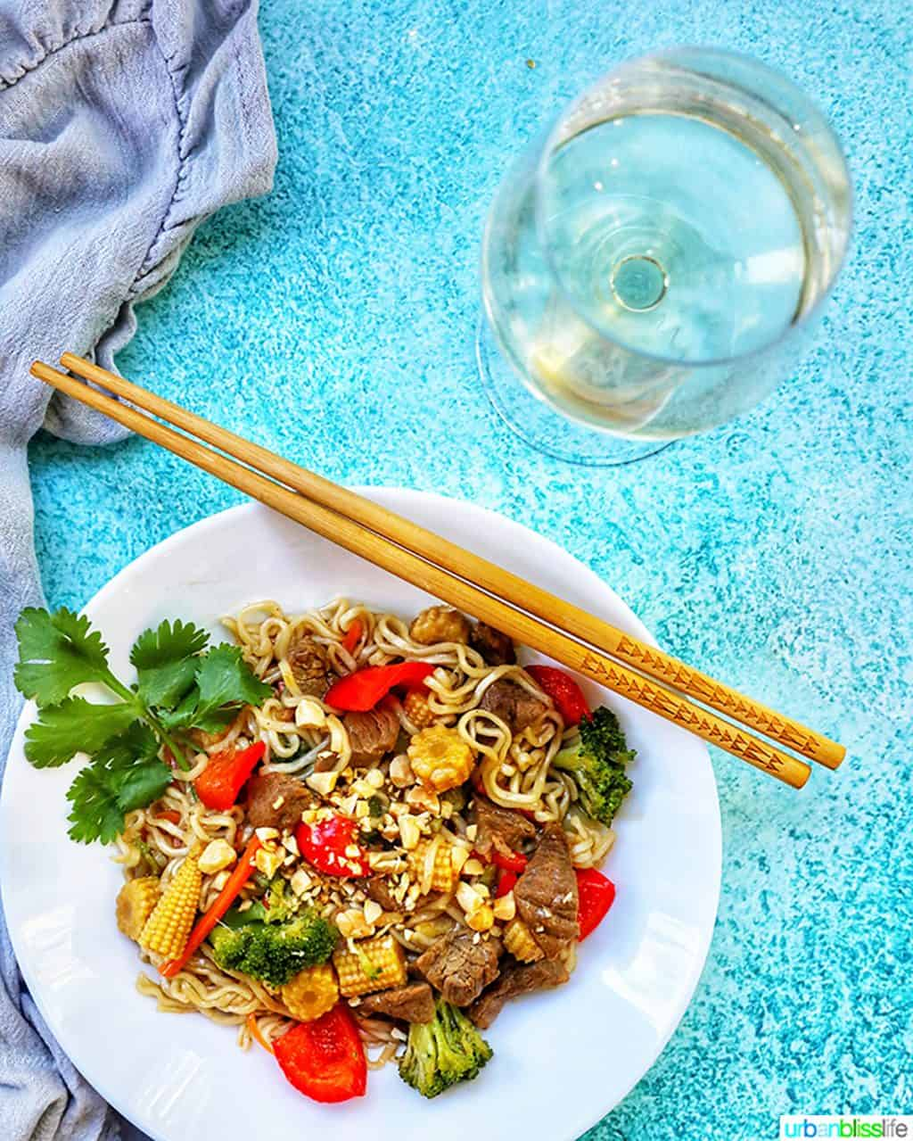 glass of white wine with bowl of beef lo mein noodles and chopsticks