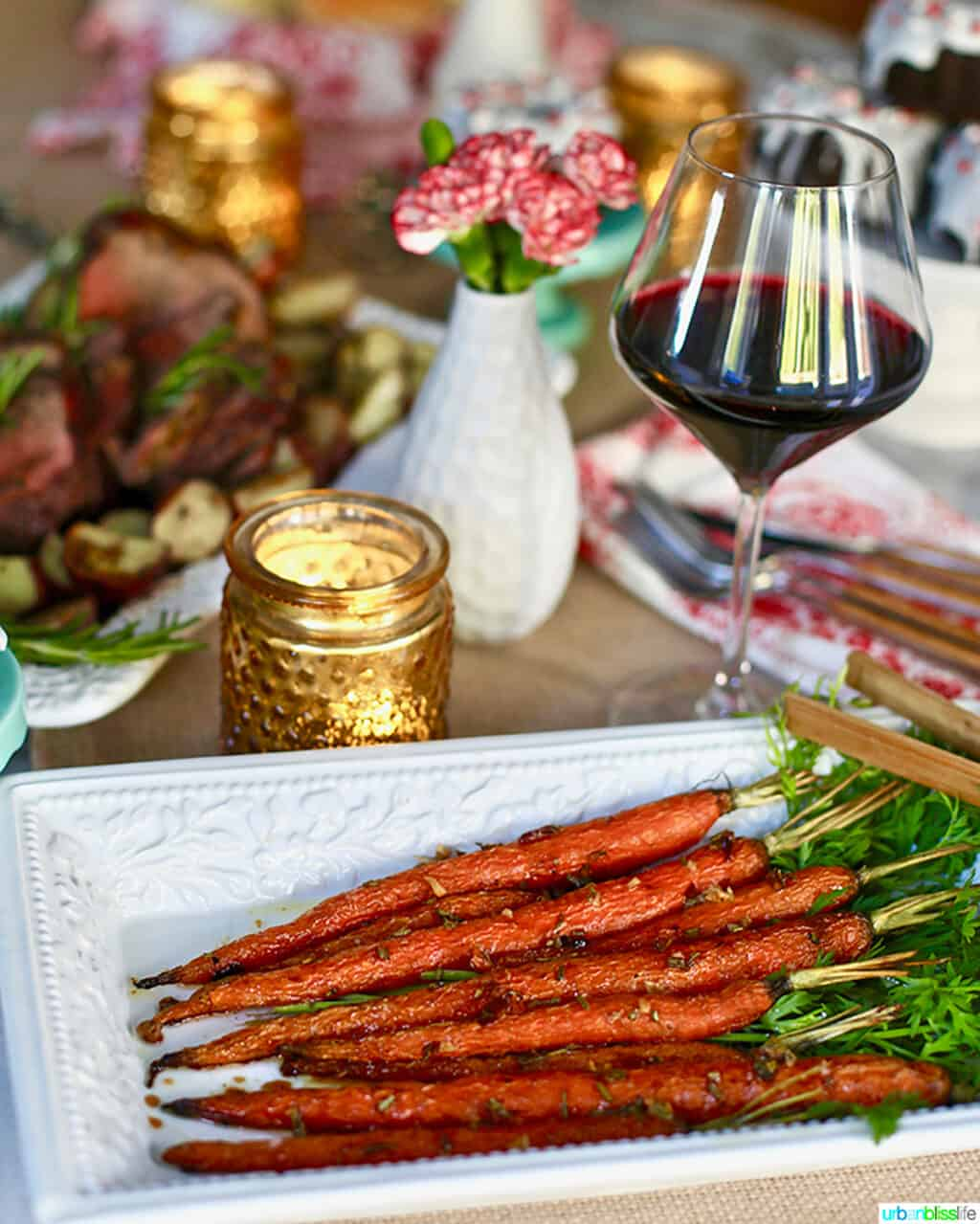 plate of garlic rosemary roasted glazed carrots on holiday table with wine