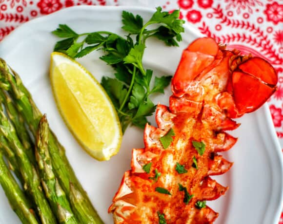 lobster tail with lemon, asparagus, white wine on red and white cloth