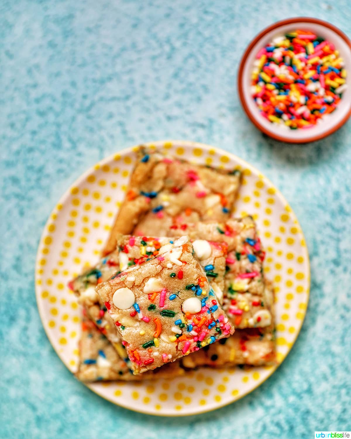 Funfetti Bars on a yellow plate with bowl of sprinkles