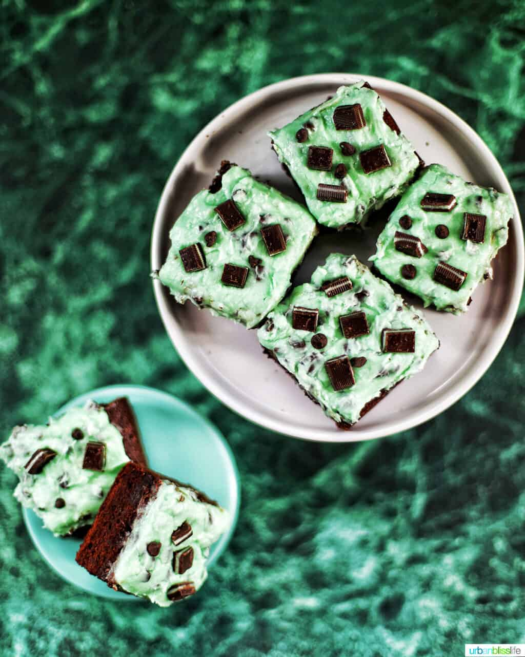 Mint Chocolate Chip Brownies on two cake pedestals on green background