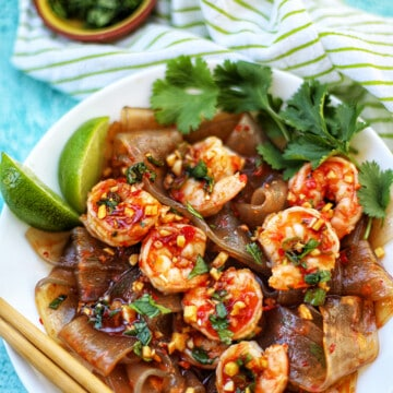 wide glass noodles with shrimp and chili lime oil sauce in a bowl with chopsticks