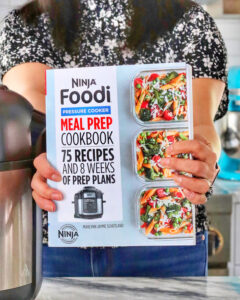 hands holding Ninja Foodi Meal Prep Cookbook