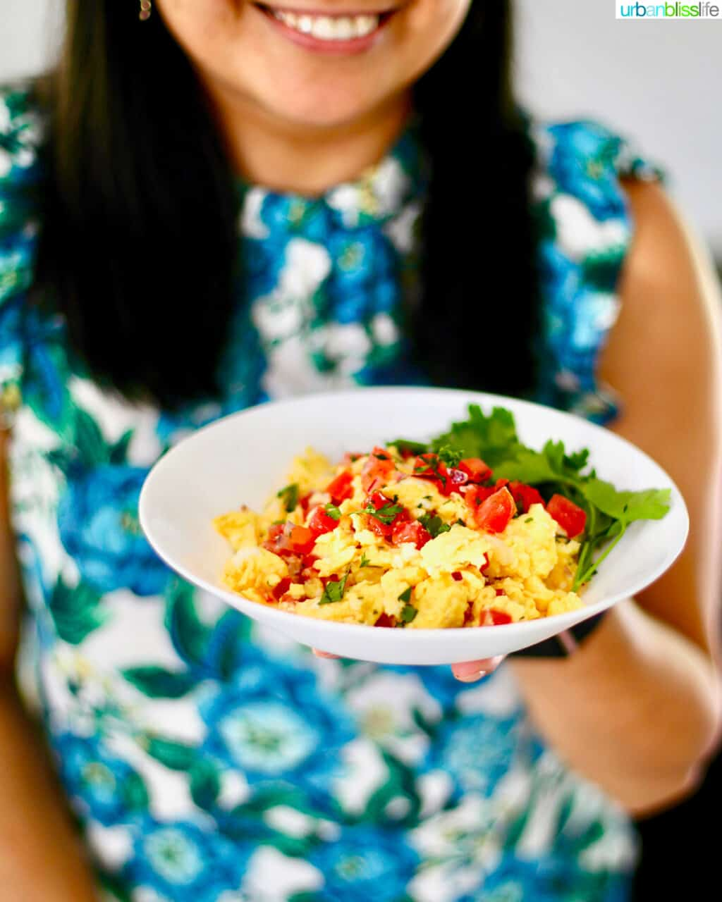 holding bowl of salsa eggs against backdrop of blue and white floral shirt